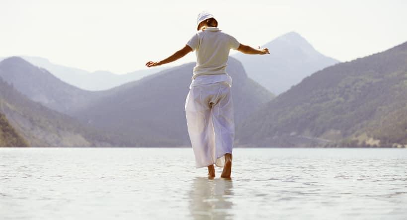 femme marchant sur l'eau en gardant l'équilibre avec ses mains avec la montagne au fond
