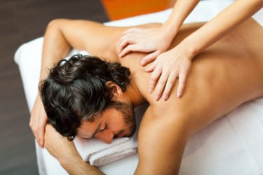 homme reposé sur une table de soin se faisant masser le dos par une femme