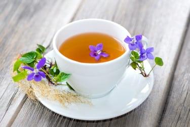 une tasse de tisane avec des fleurs violettes