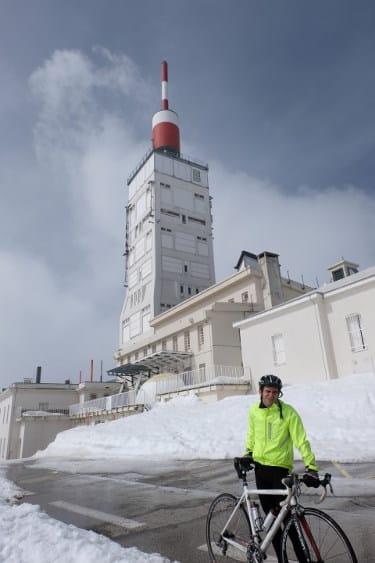 Clemens Hesse au sommet du Mont Ventoux devant la tour avec son vélo de route devant la neige