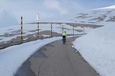 Clemens Hesse en train de monter au Mont Ventoux en vélo de route en jeûnant en roulant sur un couloir étroit de route lnogé de neige, peu de kilomètres avant l'arrivée avec la tour du sommet en vue