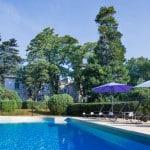 La piscine du domaine Le Colombier avec la maison de maître au fond