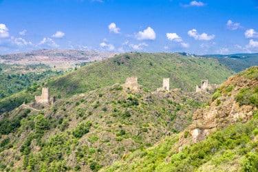 vue panoramique sur des ruines de chateaux Cathares alignés sur une crête de montagne entourés d'arbres et de roches