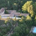 Le domaine du Monastère de Ségriès vu du ciel avec sa piscine, le cloître et la chapelle, entouré d'arbres en pleine nature
