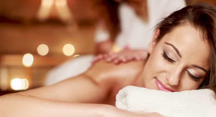 femme souriante et détendue avec les yeux clos allongé sur son dos sur une table de massage recevant un soin éngergétique par un homme par ses mains avec un paravent au fond