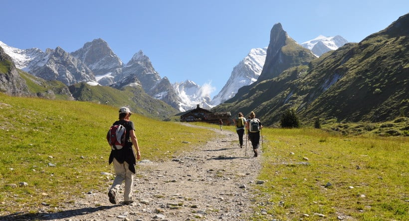 quatre randonneurs s'approchant sur une piste au refuge des barmettes à pralognan en vanoise dans les alpes avec les montagnes du col de la vanoise au fond