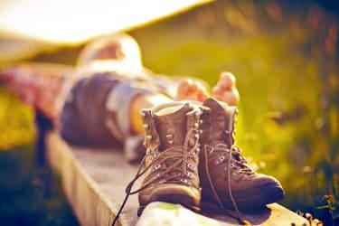 homme couché sur un banc faisant une sieste pendant une randonnée avec ses chaussures en premier plan