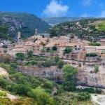Vue de loin sur un village dans le Pays Cathare avec un rivière et des vignes au premier plan et des gorges au fond