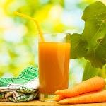un verre de jus de carottes frais avec une paille trois carottes et un torchon